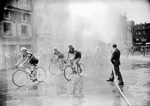 As the cyclists pass through a small town on 3 July 1957 they are sprayed with water from a firehose to help cool off